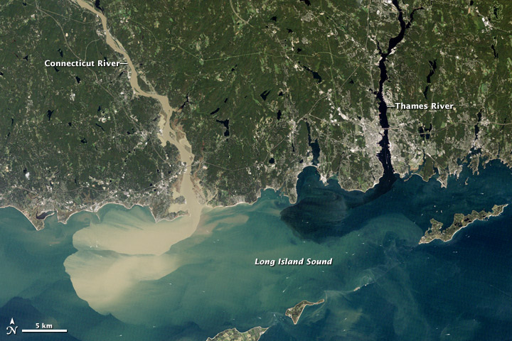 Aerial view in New England showing brown flood water entering ocean.  It is brown from the sediments